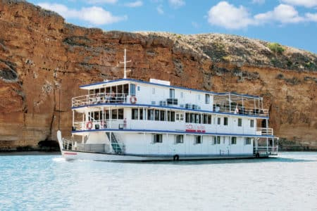 Proud Mary sailing by sandstone cliffs